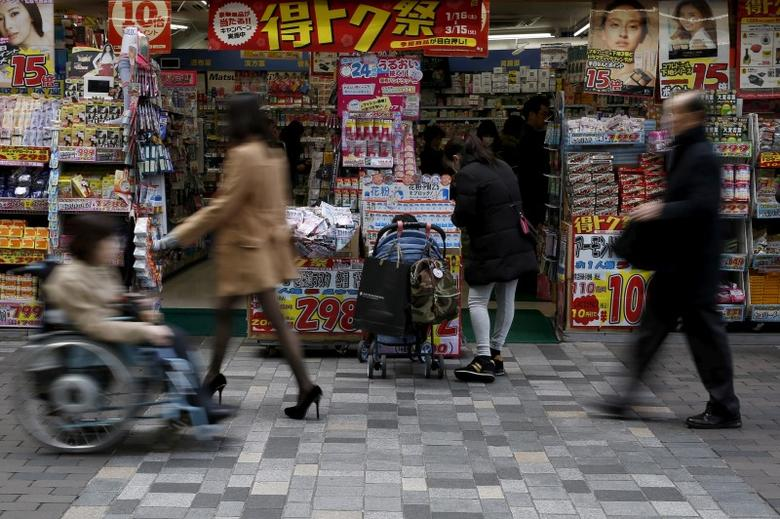 A woman with a baby buggy looks at items outside a discount store at a shopping district in Tokyo, Japan, February 25, 2016. REUTERS/Yuya Shino/File Photo