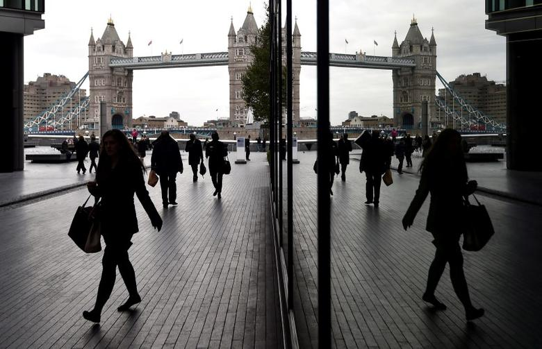 Workers walk through the More London business district with Tower Bridge seen behind in London, Britain, November 11, 2015.  REUTERS/Toby Melville/File Photo