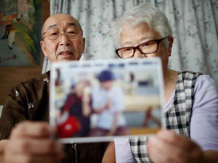 Takashi Ono (L) and his wife Chikiko, parents of 43-year-old Kazuya, a long time resident of the Tsukui Yamayuri-en facility who survived multiple stabbing  wounds in the attack at a facility for disabled people in July 2016, hold a photo of Kazuya and Chikiko  during an interview with Reuters at their home in Zama, Kanagawa prefecture, Japan September 7, 2016. Picture taken September 7, 2016.  REUTERS/Issei Kato