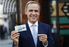 Bank of England governor Mark Carney poses with a new polymer five pound note at Whitecross Street Market in London, Britain September 13, 2016. REUTERS/Stefan Wermuth