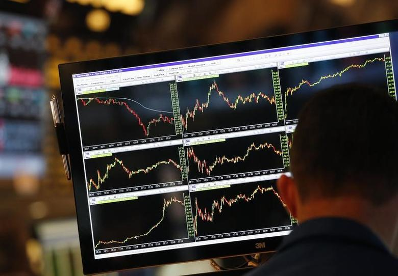 A screen displays stock charts while a trader works at his post on the floor at the New York Stock Exchange, May 30, 2013.  REUTERS/Brendan McDermid