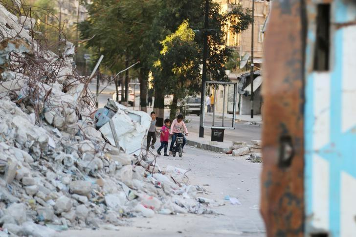 Children play with a bicycle near the rubble of damaged buildings in the rebel-held Bab al-Hadid neighbourhood of Aleppo, Syria, September 14, 2016. REUTERS/Abdalrhman Ismail