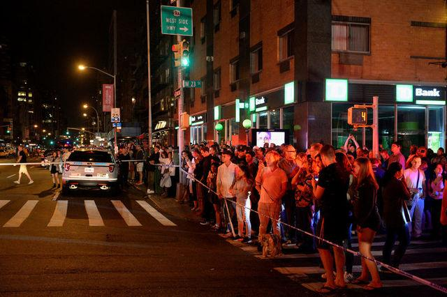 Onlookers stand behind a police cordon near the site of an explosion in the Chelsea neighborhood of Manhattan, New York, U.S.  September 17, 2016.  REUTERS/Rashid Umar Abbasi
