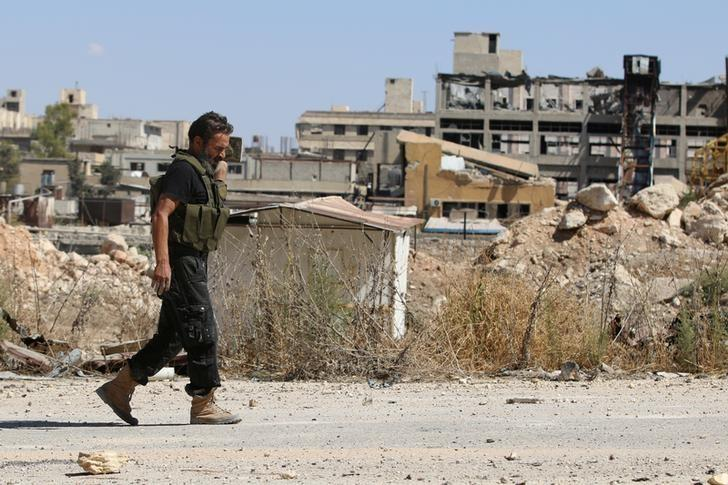 A rebel fighter walks by damaged buildings near Castello road in Aleppo, Syria September 16, 2016. REUTERS/Abdalrhman Ismail