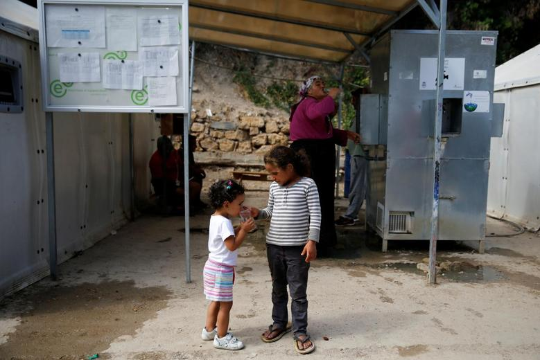 A girl from Syria gives a glass of water to her sister at the Souda municipality-run camp for refugees and migrants, on the island of Chios, Greece, September 7, 2016. REUTERS/Alkis Konstantinidis