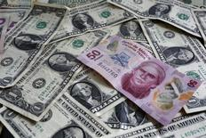 Ilustración fotográfica de un billete de 50 pesos mexicanos junto a billetes de 1 dólar, jul 6, 2015. Las monedas latinoamericanas continuarían adentrándose esta semana en zona de turbulencias, con volatilidad creciente y más caídas a la vista, a la espera de la decisión de las tasas de interés de Estados Unidos y las encuestas antes de las elecciones que se celebran allí en noviembre.  REUTERS/Edgard Garrido