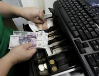 Продавец раскладывает рублевые банкноты в кассе. Реальная заработная плата в РФ в августе 2016 года сократилась на 5 процентов к предыдущему месяцу и на 1 процент к августу 2015 года, составив в номинальном выражении 34.095 рублей, сообщилРосстат.  REUTERS/Ilya Naymushin