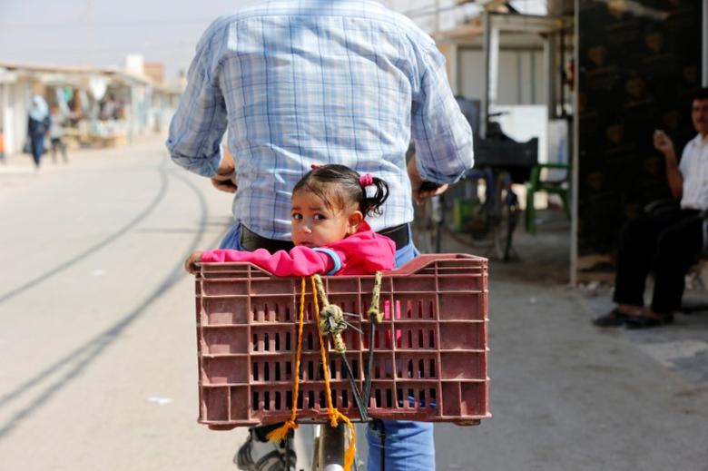 A Syrian refugee rides a bicycle with his daughter at the main market, in the Al-Zaatri refugee camp in the Jordanian city of Mafraq, Jordan, near the border with Syria. REUTERS/Muhammad Hamed