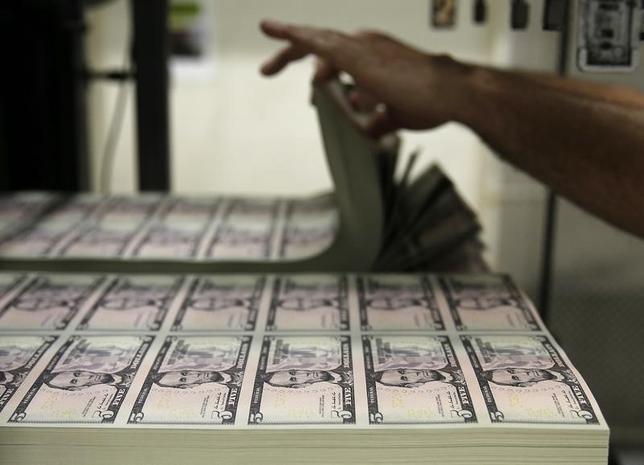 9月19日、ニューヨーク市場でドルは下落。日銀と米FRBが今週の会合でドル高につながる政策決定には動かないとの見方が優勢になった。ワシントンの財務省印刷局で印刷される5ドル紙幣、昨年撮影(2016年 ロイター/Gary Cameron)
