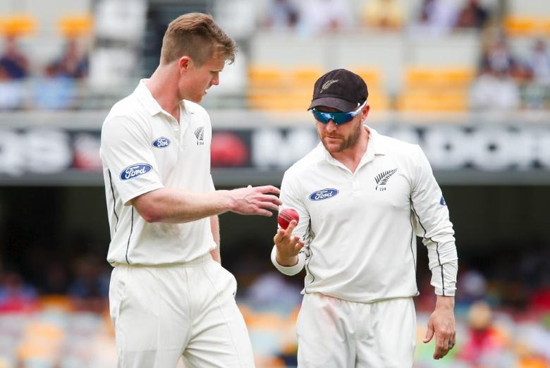 New Zealand bowler Jimmy Neesham (L) receives the ball from his captain Brendon McCullum during the first cricket test match between Australia and New Zealand in Brisbane November 6, 2015. REUTERS/Patrick Hamilton - RTX1UZ0V