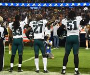 Sep 19, 2016; Chicago, IL, USA; Philadelphia Eagles defensive back Ron Brooks (33), strong safety Malcolm Jenkins (27) and defensive end Steven Means (51) raise their right hands up during the playing of the national anthem prior to the game against the Chicago Bears at Soldier Field. Mandatory Credit: Mike DiNovo-USA TODAY Sports