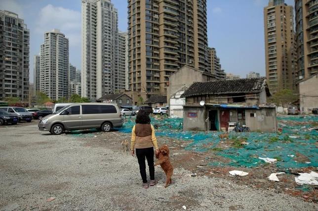 9月19日、中国の住宅価格はバブル状態にあり、いつ破裂してもおかしくない。写真は上海の光復里地区で犬を連れて歩く女性。4月撮影(2016年 ロイター/Aly Song)