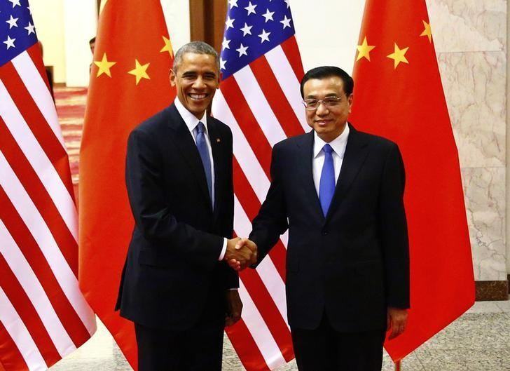 U.S. President Barack Obama (L) shakes hands with China's Premier Li Keqiang in front of U.S. and Chinese national flags during a meeting at the Great Hall of the People in Beijing November 12, 2014. REUTERS/Petar Kujundzic/Files