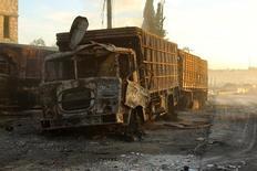 Сгоревший грузовик в удерживаемом повстанцами городе Урм аль-Кубра к западу от Алеппо 20 сентября 2016 года. Сирийские или российские самолеты нанесли удар по конвою гуманитарной помощи вблизи Алеппо в понедельник, сообщили наблюдатели, после того как сирийские военные объявили об окончании режима прекращения огня, согласованного при посредничестве США и России. REUTERS/Ammar Abdullah