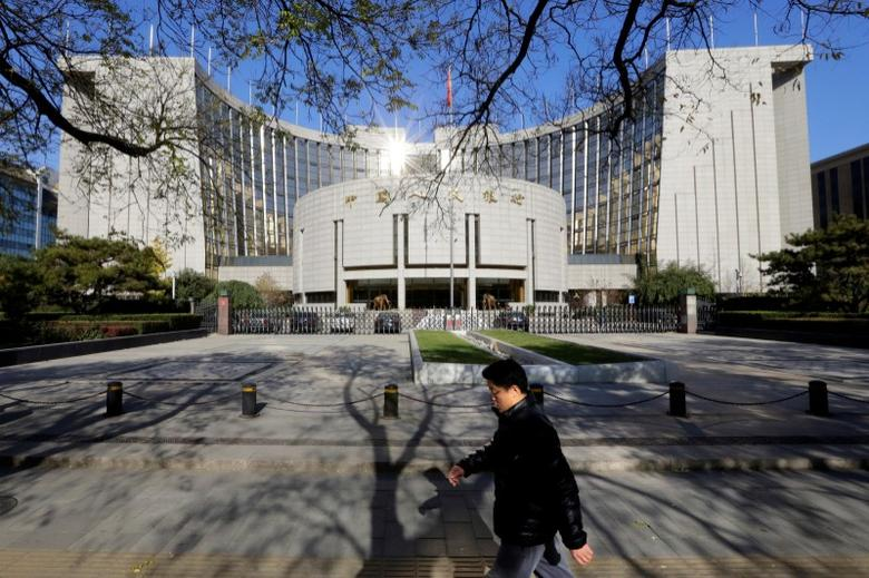 A man walks past the headquarters of the People's Bank of China (PBOC), the central bank, in Beijing November 20, 2013.  REUTERS/Jason Lee/File Photo