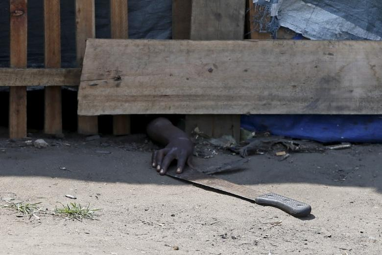 A protester, hiding from police, tries to retrieve a machete during a protest against President Pierre Nkurunziza's decision to run for a third term in Bujumbura, Burundi, May 29, 2015. REUTERS/Goran Tomasevic