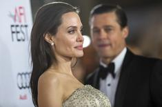 "Director and cast member Angelina Jolie poses, as her husband and co-star Brad Pitt stands nearby, at the premiere of ""By the Sea"" during the opening night of AFI FEST 2015 in Hollywood, California November 5, 2015. The movie opens in the U.S. on November 13. REUTERS/Mario Anzuoni"