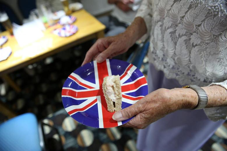 A woman carries a prawn sandwich on a Union Jack-coloured paper plate at the Clacton United Kingdom Independence Party (UKIP) Committee Brexit party in Clacton-on-Sea, a town in eastern England, where 70 percent of people voted on June 23, 2016 to leave the European Union, Britain August 25, 2016. REUTERS/Neil Hall/Files