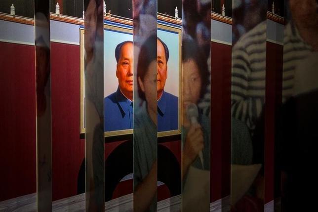 9月20日、中国政府は汚職取り締まりの一環で、中国で汚職に関与し、国外に逃亡した当局者の不正に取得した資産を回収する取り組みを海外で強化する。写真は香港・尖沙咀にある美術館に展示されている故・毛沢東首席と天安門事件の首謀格学生のポートレイト。2014年4月撮影(2016年 ロイター/Tyrone Siu)