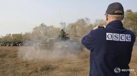 Член ОБСЕ в так называемой Луганской народной республике в Стаханове 20 октября 2015 года. Украинская армия и пророссийские сепаратисты в Донбассе вслед за тяжелыми вооружениями попробуют зачехлить и стрелковое оружие: для начала в трех поселениях, а если получится - то по всей 500-километровой линии разграничения, сообщил посредник в переговорах из ОБСЕ. REUTERS/Alexander Ermochenko