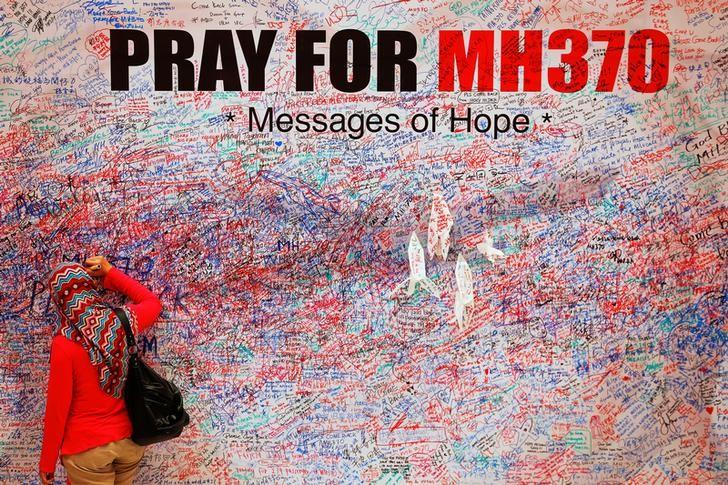 FILE PHOTO: A woman leaves a message of support and hope for the passengers of the missing Malaysia Airlines MH370 in central Kuala Lumpur March 16, 2014.  REUTERS/Damir Sagolj/Files