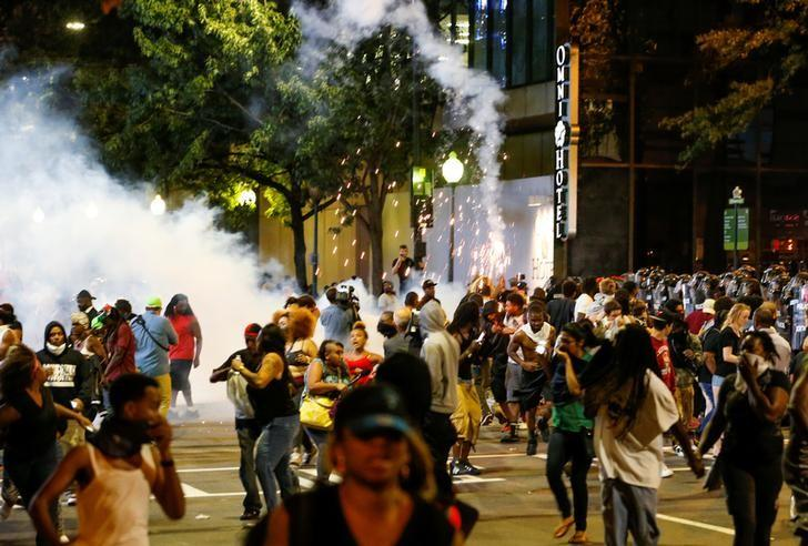 People run from flash-bang grenades in uptown Charlotte, NC during a protest of the police shooting of Keith Scott, in Charlotte, North Carolina, U.S. September 21, 2016. REUTERS/Jason Miczek     TPX IMAGES OF THE DAY
