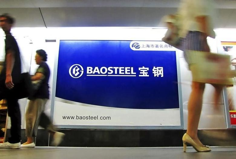 People walk past an advertising board of Baosteel Group in Shanghai, September 9, 2011.  REUTERS/China Daily