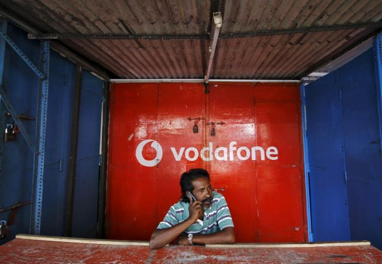 A retail shop owner speaks on his mobile phone outside his closed shop shutters painted with an advertisement for Vodafone at a market in the southern Indian city of Chennai December 30, 2013.  REUTERS/Babu/File photo