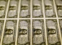 Billetes de un dólar sobre una mesa de luz en la Casa de Moneda de los Estados Unidos en Washington, nov 14, 2014. El dólar caía el jueves y tocó su nivel más bajo en más de una semana frente a una cesta de monedas importantes, luego de que los inversores vendieron la divisa tras la decisión de la Reserva Federal de Estados Unidos de reducir las estimaciones sobre sus tasas de interés a largo plazo.  REUTERS/Gary Cameron/File Photo