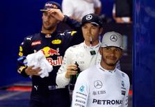 Formula One - Singapore Grand Prix - Marina Bay, Singapore - 17/9/16 Mercedes' driver Lewis Hamilton of Britain (R), Mercedes' driver Nico Rosberg of Germany (C) and Red Bull's driver Daniel Ricciardo of Australia celebrate finishing their qualifying session. REUTERS/Edgar Su