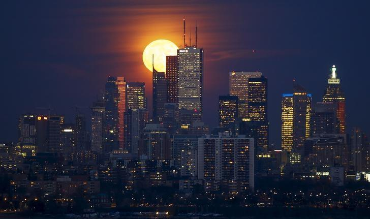 The moon rises behind the skyline and financial district in Toronto, November 25, 2015.    REUTERS/Mark Blinch