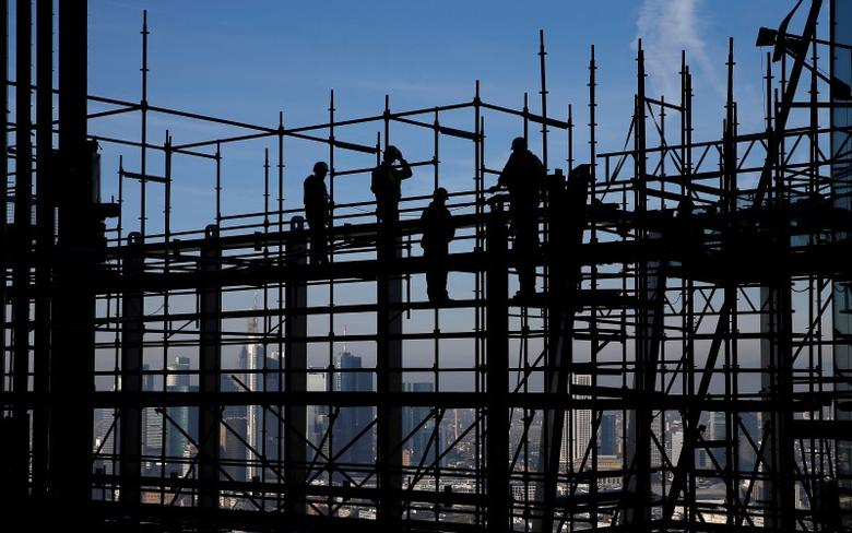 Construction workers are silhouetted while standing on scaffolding at the construction site of the new headquarters of the European Central Bank (ECB) during a guided media tour in Frankfurt, October 31, 2013. REUTERS/Kai Pfaffenbach/File photo