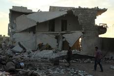 Люди исследуют разрушенное здание после авианалетов в районах Алеппо. Военные самолёты нанесли удары по удерживаемым повстанцами районам на востоке Алеппо в пятницу на второй день масштабных бомбардировок через несколько часов после того, как сирийская армия объявила о начале военной операции, сообщили спасатели и активисты.  REUTERS/Ammar Abdullah