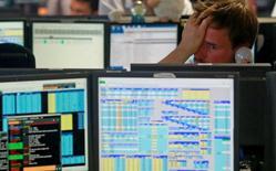 Трейдер компании BGC в лондонском финансовом центре  Canary Wharf. Европейские фондовые рынки начали торги понедельника отрицательной динамикой индексов, поскольку снижение акций крупных банков и энергетических компаний оказало давление на биржи региона.    REUTERS/Russell Boyce/File Photo