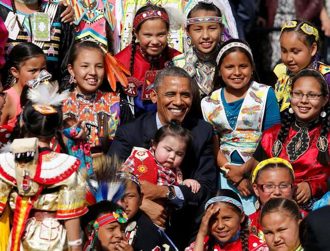 President Obama holds a baby as he poses with children at the Cannon Ball Flag Day Celebration at the Cannon Ball Powwow Grounds on the Standing Rock Sioux Reservation in North Dakota. REUTERS/Larry Downing