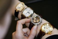 A saleswoman shows off brands belonging to Swiss Swatch Group (L-R) Breguet, Longines, Omega and Glashuette in a watch and jewellery shop in Zurich, in this March 22, 2006 file photo.  REUTERS/Siggi Bucher/Files