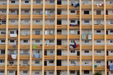 Las hipotecas sobre viviendas en España inscritas en el mes de julio bajaron un 14,9 por ciento interanual, mostraron datos del Instituto Nacional de Estadística (INE), lo que supuso cortar con una racha de 25 meses al alza. En la imagen, una mujer tiende la ropa en un edificio de Málaga, España, el 1 de julio de 2016. REUTERS/Jon Nazca