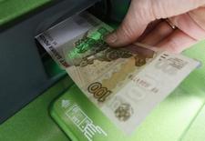 Женщина вносит деньги в банкомат Сбербанка. Банк России закладывает в свой базовый макроэкономический сценарий рост депозитов физических и юридических лиц в банках примерно на 12 процентов в 2016 году и на 7-9 процентов в 2017 году.  REUTERS/Ilya Naymushin