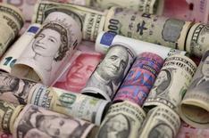 Банкноты разных стран. Зависимые от сырья валюты твёрдо держались своих позиций после того, как нефтяной картель ОПЕК договорился о сокращении добычи нефти впервые с 2008 года, что способствовало росту цен на нефть, а всеобщее увеличение спроса на рисковые активы ухудшило положение иены. REUTERS/Jason Lee/Illustration/File Photo