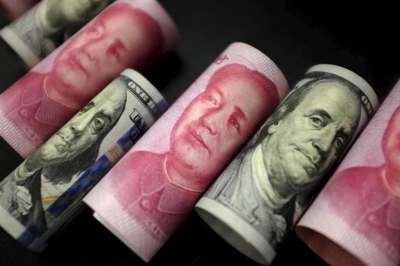2016年1月21日,百元面值的人民币和美元纸币。REUTERS/Jason Lee
