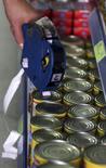 Funcionário coloca etiqueta de preço em latas de produto em supermercado de São Paulo. 08/01/2016  REUTERS/Paulo Whitaker