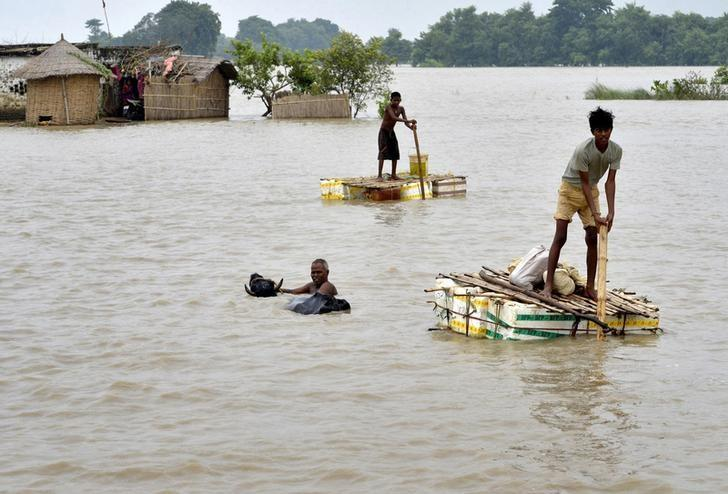 Flood-affected villagers use temporary rafts as they navigate through the floodwaters of river Ganges and move to safer grounds, after heavy rains at Patna district in Bihar August 29, 2013.  REUTERS/Krishna Murari Kishan/Files