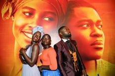 """Actors Lupita Nyong'o (L), Madina Nalwanga (C) and David Oyelowo pose in the same manner as they appear on the movie poster seen behind him during the Los Angeles premiere of """"Queen of Katwe"""" in Hollywood, California September 20, 2016. REUTERS/Danny Moloshok"""