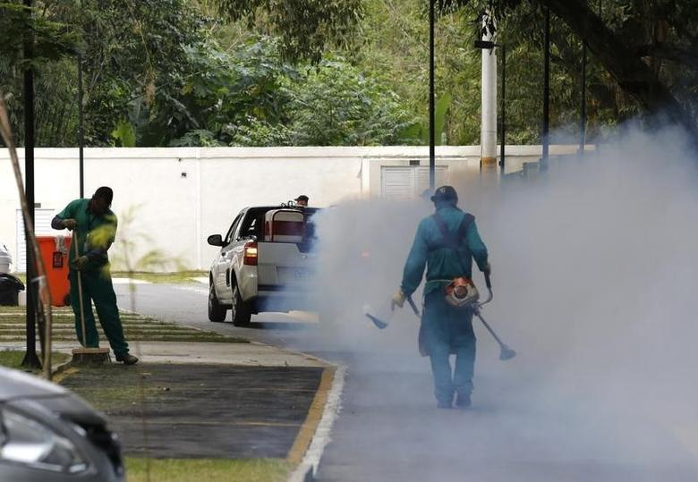 A truck sprays insecticide near grounds workers at Olympic media accomodations as part of preventive measures against the Zika virus and other mosquito-borne diseases, in Rio de Janeiro, Brazil August 29, 2016. REUTERS/Chris Helgren/Files