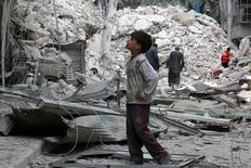 Мальчик изучает разрушения после авиаудра по удерживаемому повстанцами пригороду Алеппо, Сирия, 23 сентября 2016 года. Российские военные останутся в Сирии на неопределенное время, сообщил в пятницу Кремль, с которым США грозят прервать обсуждение кризиса в знак протеста против бомбежек Алеппо. REUTERS/Abdalrhman Ismail