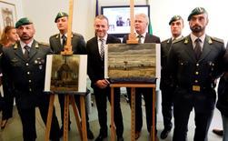Agentes de la Guardia di Finanza italiana posan junto a dos pinturas del artista holandés Vincent Van Gogh, que fueron robadas hace 14 años en Ámsterdam, durante una conferencia de prensa en Nápoles. 30 septiembre 2016. Las dos pinturas, valoradas en millones de euros, fueron halladas en una casa rural en Italia propiedad de un supuesto narcotraficante de la mafia, informó la policía REUTERS/Ciro De Luca