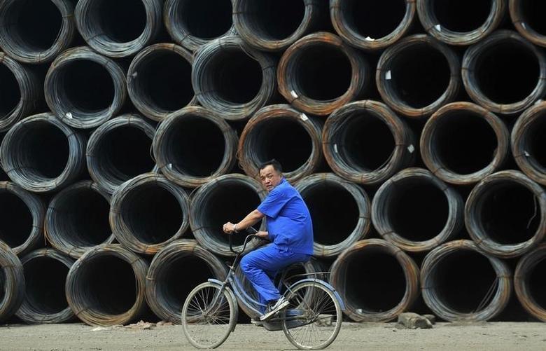 2012年6月26日,沈阳钢材批发市场,一名工人骑车经过一堆钢筋。REUTERS/Stringer