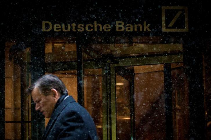 A man walks past the Deutsche Bank offices during a snow storm in Manhattan's financial district in New York January 21, 2014.   REUTERS/Brendan McDermid/Files