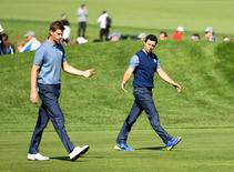 Sep 30, 2016; Chaska, MN, USA;  Rory McIlroy of Northern Ireland and  Thomas Pieters of Belgium on the first hole in the afternoon four-ball matches during the 41st Ryder Cup at Hazeltine National Golf Club. Mandatory Credit: John David Mercer-USA TODAY Sports