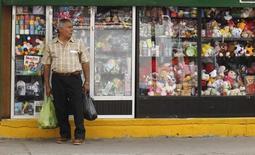 Un hombre con bolsas de compras frente a una tienda en Macas, Ecuador. 5 de noviembre de 2014. La economía de Ecuador se contrajo un 2,2 por ciento en el segundo trimestre del 2016 frente a igual periodo del año anterior, informó el lunes el Banco Central de la nación sudamericana. REUTERS/Guillermo Granja